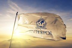 International Criminal Police Organization INTERPOL flag textile cloth fabric waving on the top sunrise mist fog. Beautiful royalty free stock photos