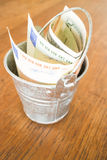 International currencies bank note in the bucket Stock Photos