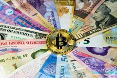 International currency bitcoin Conceptual image of bitcoin internationalism. Physical coin bitcoin on the banknotes of royalty free stock photo