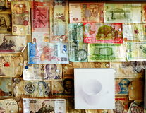 International Currency and Coffee Cup. Various currency bills pinned to a wall along with a picture of a coffee cup Stock Images
