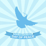 International day of peace vector illustration with dove, olive branch and ribbon on rays background. Stock Image