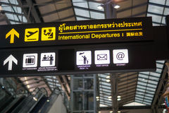International departures - illuminated yellow sign at airport Stock Images