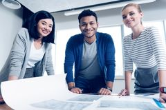 International engineer standing between his female colleagues. Inspiration. Handsome male person keeping smile on his face and leaning on fists while posing on stock images