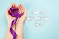 International Epilepsy Day. International or world Epilepsy Day concept. The text and a purple ribbon with female hands on a white wooden table background. The royalty free stock images