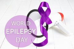 International Epilepsy Day. International or world Epilepsy Day concept. The text and a purple ribbon with megaphone on a white wooden table background. The royalty free stock photo