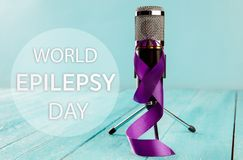 International Epilepsy Day. International or world Epilepsy Day concept. The text and a purple ribbon with microphone on a wooden table background. The health royalty free stock photography