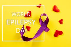 International Epilepsy Day. International or world Epilepsy Day concept. The text and a purple ribbon on a yellow background. The health, breast, awareness royalty free stock images