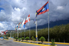 International Flags next to road. Flags waved under cloudy sky. International center of development in Otavalo, Ecuador Stock Images