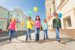 International friends with colorful balloons walk. International looking friends kids with colorful balloons walking together in city centre during summer time Stock Image