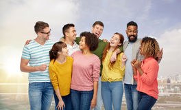International group of happy laughing people. Diversity, race, ethnicity and people concept - international group of happy men and women laughing over singapore Royalty Free Stock Photos