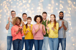International group of happy people applauding. Diversity, race, ethnicity and people concept - international group of happy smiling men and women applauding Royalty Free Stock Photos