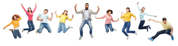International group of happy people jumping. Happiness, freedom, motion, diversity and people concept - international group of happy smiling men and women Stock Photos
