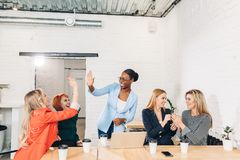 International group of happy women celebrating success at team meeting royalty free stock images