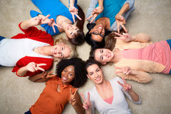 International group of happy women showing peace. Diversity, race, ethnicity and people concept - international group of happy smiling different women lying on Royalty Free Stock Images