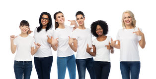 International group of women in white t-shirts. Diversity, race, ethnicity and people concept - international group of happy smiling different women pointing to Royalty Free Stock Photo