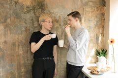 International handsome homosexual men drinking coffee and looking at each other at the kitchen. Wearing casual clothes. Blonde asian men in eyeglasses and stock photos