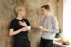 International handsome homosexual men drinking coffee and looking at each other at the kitchen. Wearing casual clothes. Blonde asian men in eyeglasses and royalty free stock image