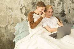 International homosexual male couple enjoying leisure time together. In one bed and watching online movie on laptop computer, monochrome interior royalty free stock photography