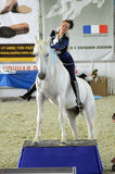 International Horse Show. Woman jockey in blue dress Female rider on a white horse. Royalty Free Stock Photo