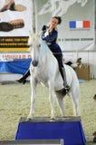 International Horse Show. Woman jockey in blue dress Female rider on a white horse. Royalty Free Stock Photo