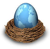 International Investments. And global finance business symbol with a blue egg with the map of the world in a nest as a concept of savings and money management Royalty Free Stock Photos