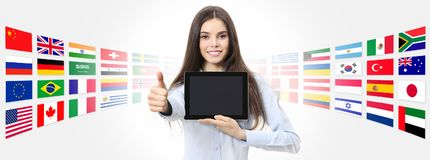 International language school concept smiling woman with like th. Umb up showing digital tablet on global flags background royalty free stock photos