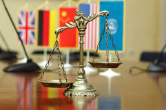 International Law and Order. Decorative Scales of Justice with blurred National flag of different countries, concept of International Law and Order, focus on the Stock Photography