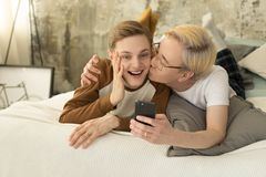 International love. Homosexual asian man with blonde hair kissing his european boyfriend and taking selfie photo. International love. Homosexual asian men with royalty free stock images