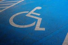 International markings for a handicapped parking, Disabled symbol sign on blue asphalt in parking space. Close up International markings for a handicapped Royalty Free Stock Images