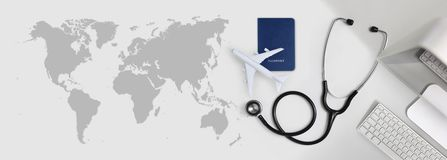 International medical travel insurance concept, stethoscope, passport, computer and airplane in desk office banner with global map. International medical travel royalty free stock photo