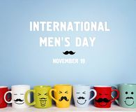 International men`s day background with colorful mugs with a mus stock photography