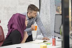International multicultural team at work: asian muslim woman and caucasian man. stock photography
