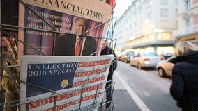 International newspapers about Donald Trump new USA president. PARIS, FRANCE - NOV 10, 2016: Man buying Financial Times newspaper with shocking headline title at