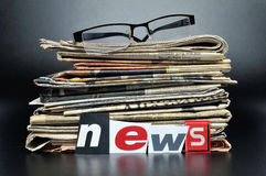 International Newspapers. Stack of newspapers with glasses on top and the lettering NEWS in front Royalty Free Stock Photography