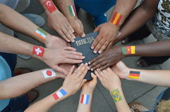 International people with flags holding a bible. International brothers and sisters in Christ with different flags painted on their arms holding a bible together Stock Image