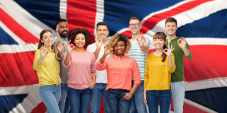 International people showing ok over british flag Royalty Free Stock Photos