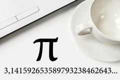 International Pi Day. On a white table a laptop and a cup. Large text and numbers stock photo
