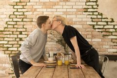 International romantic hot same-sex couple kiss each other across the table at home royalty free stock photos