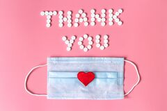 International`s nurses week concept, Text Thank you by tablets and red heart on pink background.