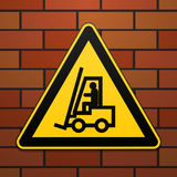 International safety warning sign. Carefully, lift truck The sign on the brick wall background. Black image on a yellow triangle. Royalty Free Stock Photos