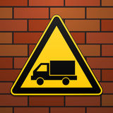 International safety warning sign. Watch out for the car The sign on the brick wall background. Black image on a yellow triangle. Royalty Free Stock Photos