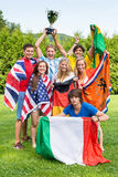 International Sports fans winning the cup. Group of international sports fans, each dressed in the color of their country and carrying the their nation's flag Royalty Free Stock Photo
