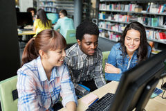 International students with computers at library Royalty Free Stock Photos