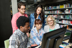 International students with computers at library Royalty Free Stock Images