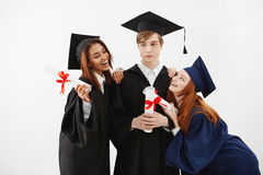 International students graduates rejoicing smiling posing over white background. Stock Image