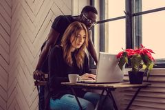 International students with laptop. African american male and caucasian female using laptop at the table Stock Images