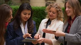 International students paying with card with tablet in slow motion near university building.n. International students paying by tablet with card in slow motion stock footage