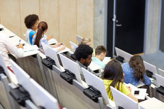 International students at university lecture hall. Education, high school, university, learning and people concept - group of international students talking in royalty free stock image