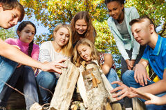 International teens construct bonfire together. Near yellow tent during autumn day in the forest Stock Images