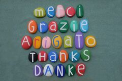 International thanks in different languages with stone colored letters over green sand